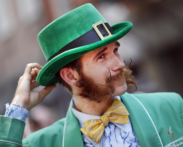 Pierre Dupleix of New Orleans, a bartender at the famed Pat O'Brien's bar in the French Quarter, adjusts his hat while participating in a parade through the French Quarter kicking off the fourth annual Just For Men National Beard and Moustache Championships Saturday, September 7, 2013 in New Orleans. Dupleix said it took him five months to grow his sideburns. Contestants competed in 18 different categories including Dali, full beard natural and sideburns. (Photo by Susan Poag/AP Photo)