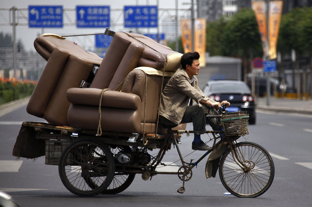 A man rides a tricycle loaded with lounge chairs along a road in Beijing June 5, 2012. (Photo by David Gray/Reuters)