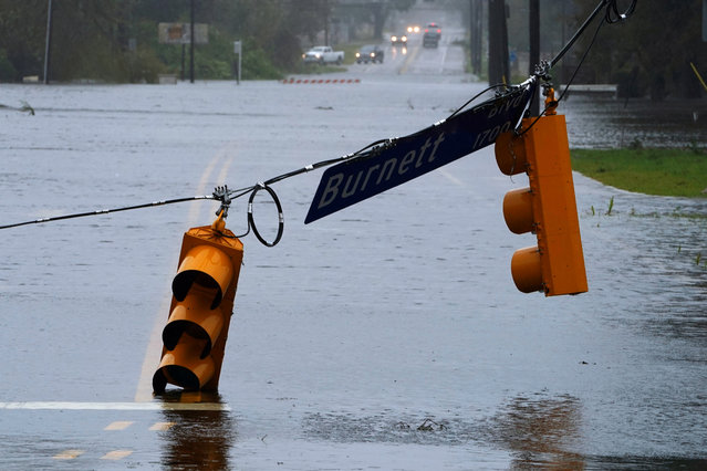 A street light is downed on a flooded road as Hurricane Florence comes ashore on Wilmington, N.C., September 14, 2018. (Photo by Carlo Allegri/Reuters)