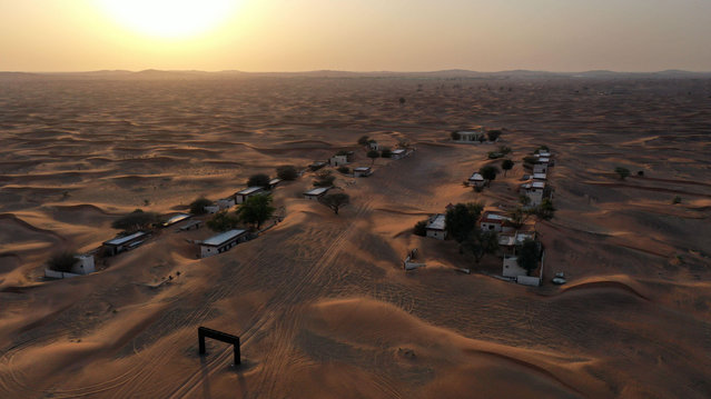 An aerial view shows the abandoned village of Al-Madam, bordering the Gulf Emirate of Sharjah, half buried in the desert sand, on April 22, 2021. (Photo by Giuseppe Cacace/AFP Photo)