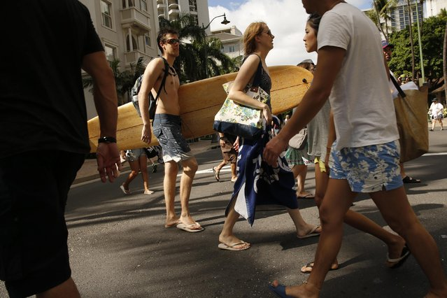 A man with a surfboard passes a city crosswalk in the heavily touristed Waikiki section of Honolulu, Hawaii January 1, 2016. (Photo by Jonathan Ernst/Reuters)