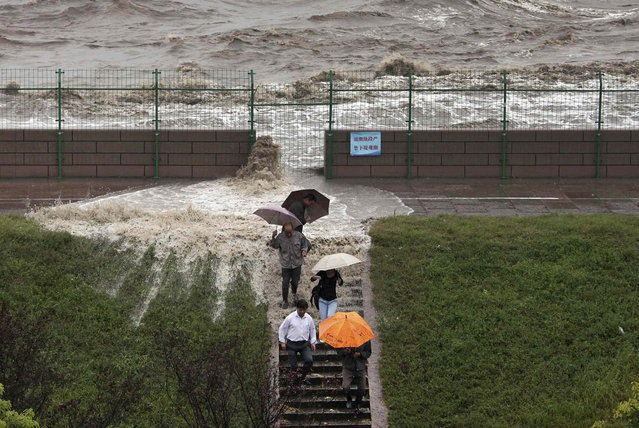Visitors run down a stairway as tidal waves under the influence of Typhoon Fitow surge past a barrier in Haining, Zhejiang province October 7, 2013. Four people were killed and hundreds of thousands evacuated after Typhoon Fitow hit eastern China, destroying houses and farmlands and closing ports and airports. (Photo by Reuters/Stringer)