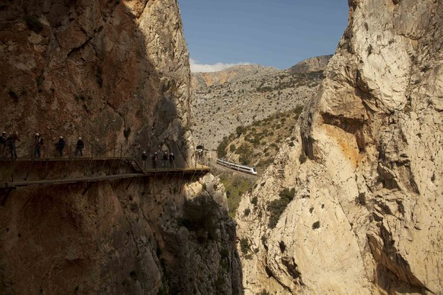 A train is seen as journalists walk along the new Caminito del Rey (The King's Little Pathway) in El Chorro-Alora, near Malaga, southern Spain March 15, 2015. (Photo by Jon Nazca/Reuters)