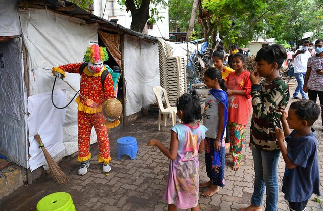 Social worker volunteer Ashok Kurmi, dressed as a clown interacts with children while he sanitises a football and spread awareness to follow the Covid-19 coronavirus safety protocols inside a slum area in Mumbai on June 2, 2021. (Photo by Indranil Mukherjee/AFP Photo)