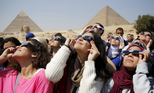 People look up to view a partial solar eclipse around the Giza Pyramids, on the outskirts of Cairo, March 20, 2015. (Photo by Amr Abdallah Dalsh/Reuters)