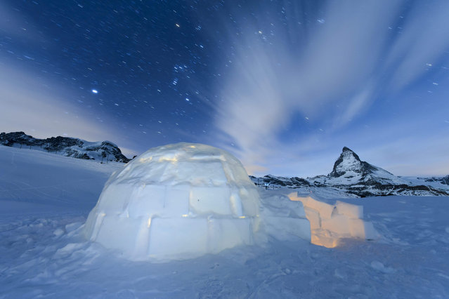 """A long time exposure shows a Igloo at the """"Igloo village"""" (Iglu Dorf) in front of the famous Matterhorn mountain in Zermatt, Switzerland, late 28 January 2016. The hotel-igloo village made of snow and ice at 2'815 meters about sea level with a bar, a restaurant, bedrooms and wellness are celebrating their 20th anniversary. (Photo by Jean-Christophe Bott/EPA)"""