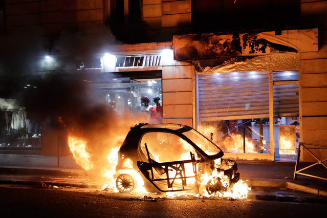 """A car burns during a protest of """"yellow vests"""" (gilets jaunes) against rising costs of living near Paris city Hall on December 8, 2018. Paris was on high alert on December 8 with major security measures in place ahead of fresh """"yellow vest"""" protests which authorities fear could turn violent for a second weekend in a row. (Photo by Thomas Samson/AFP Photo)"""