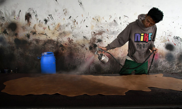 A factory worker sprays color onto a piece of leather. (Photo by Rezza Estily/JG Photo)