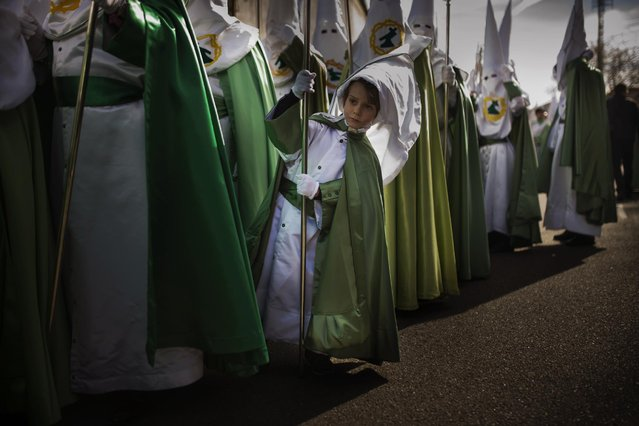 A penitent of the 'Virgen de la Esperanza' brotherhood looks as he waits for the beginning of a Holy Week procession in Zamora, Spain, Thursday, April 2, 2015. Hundreds of processions take place throughout Spain during the Easter Holy Week. (Photo by Andres Kudacki/AP Photo)