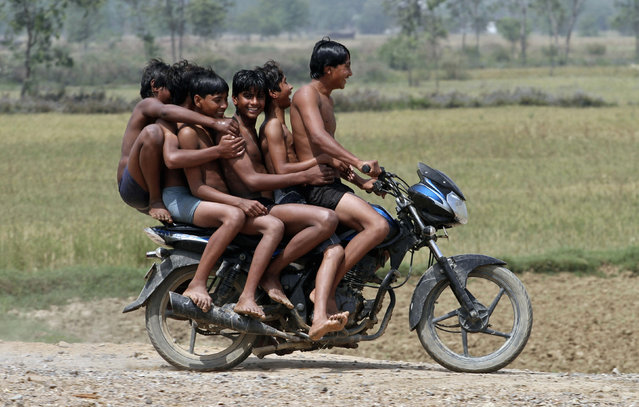 Boys ride a motorbike on their way back home after taking a bath in a canal at Chachura village, in Uttar Pradesh April 4, 2012. (Photo by Parivartan Sharma/Reuters)