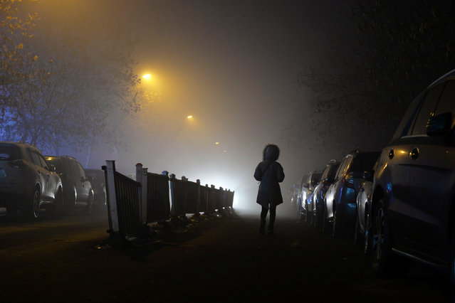 A woman walks past parked cars in heavy smog in Urumqi, Xinjiang Uighur Autonomous Region, China January 7, 2017. (Photo by Reuters/Stringer)
