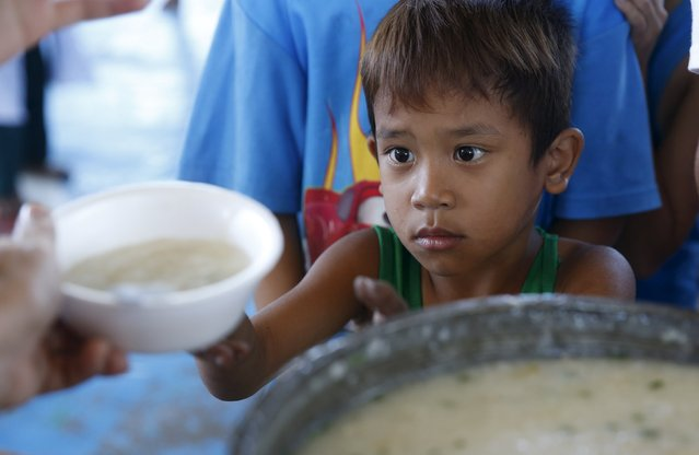 A boy receives a free hot meal at an evacuation centre for fire victims in Muntinlupa, Metro Manila February 23, 2016. (Photo by Erik De Castro/Reuters)