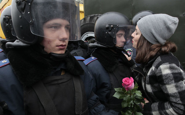 A pro-European demonstrator attempts to kiss a riot police officer in Kiev, Ukraine, Monday, December 30, 2013. Opposition activists protested in the capital maintaining more than a month of rallies opposing the government's decision to shelve a key deal with the European Union. (Photo by Sergei Chuzavkov/AP Photo)