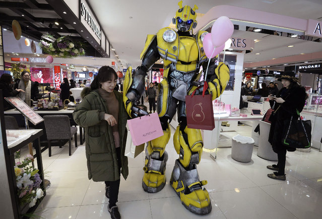 In this Thursday, February 14, 2019, photo, a Transformer's Bumblebee mascot helps a woman carries paper bags at a shopping mall in Handan in north China's Hebei province. U.S. and Chinese envoys are holding a second day of trade talks after the top economic adviser to President Donald Trump said he has yet to decide whether to go ahead with a March 2 tariff increase on imports from China. (Photo by Chinatopix via AP Photo)