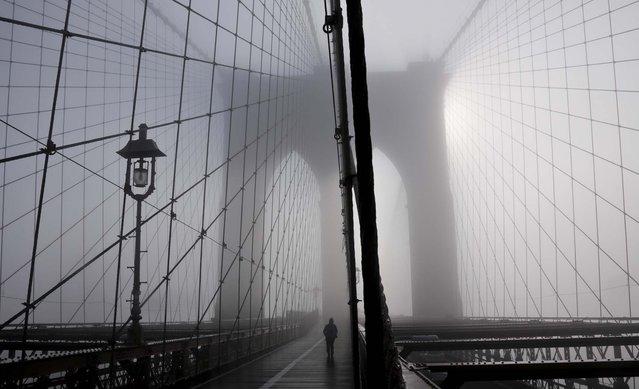 Heavy fog settles onto the Brooklyn Bridge. (Photo by Bebeto Matthews/Associated Press)