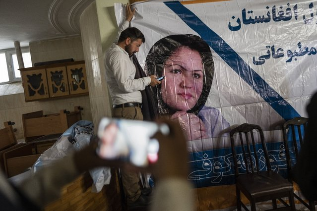 """A man holds a poster of Afghan politician Fawzia Koofi prior to a press conference organized by the """"movement of change for Afghanistan Party"""" in Kabul, Afghanistan, Sunday, September 19, 2021. (Photo by Bernat Armangue/AP Photo)"""