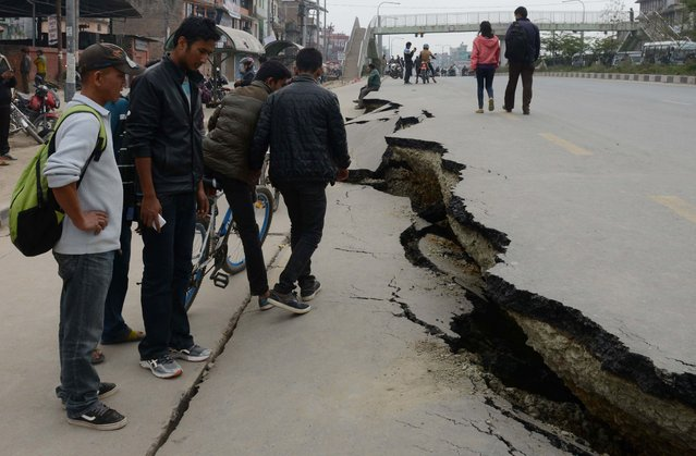Nepalese residents walk past road damage following an earthquake in Kathmandu on April 26, 2015. (Photo by Prakash Mathema/AFP Photo)