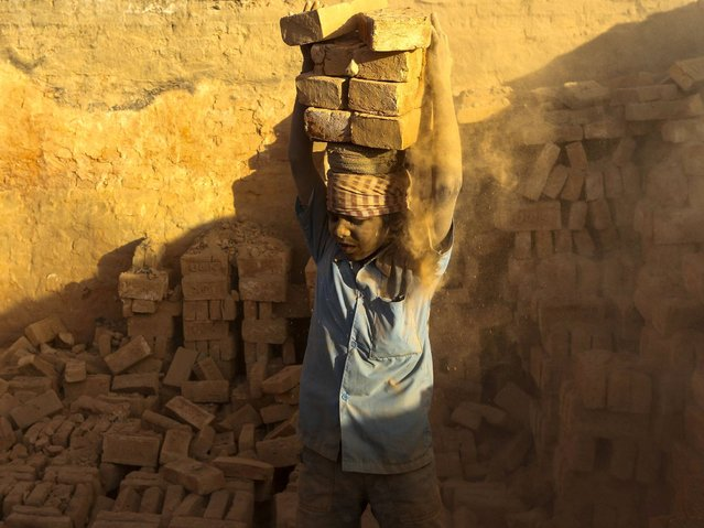 A young boy lifts heavy bricks as he works at brick factory around Kathmandu valley. (Photo by Narendra Shrestha/EPA)