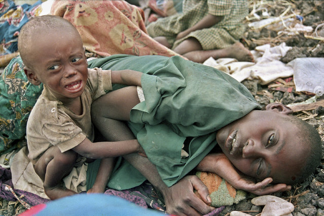 In this July 27, 1994, file photo, a Rwandan Hutu refugee child desperately tries to waken his mother from a diseased sleep in the Munigi camp outside Goma, in Zaire, now known as Congo. The scale of the killings in 1994 was unimaginable but the reporting and photographs taken at the time helped to inform the world of the horrors of the genocide. (Photo by Javier Bauluz/AP Photo/File)