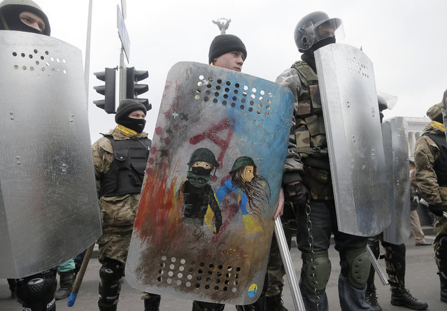 An opposition protester holds a shield depicting, what he said, is a self-portrait with his girlfriend in a sign of love on a Valentine's Day while protesters prepare for a rally in Kiev's Independence Square, the epicenter of the country's current unrest, Ukraine, Friday, February 14, 2014. (Photo by Efrem Lukatsky/AP Photo)