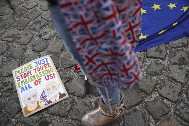 Anti-Brexit campaigner Madeleina Kay, from Sheffield, England, stands near a placard depicting British Prime Minister Theresa May and Labour leader Jeremy Corbyn as she protests outside EU headquarters in Brussels, Wednesday, April 10, 2019. European Union leaders meet Wednesday in Brussels for an emergency summit to discuss a new Brexit extension. (Photo by Francisco Seco/AP Photo)