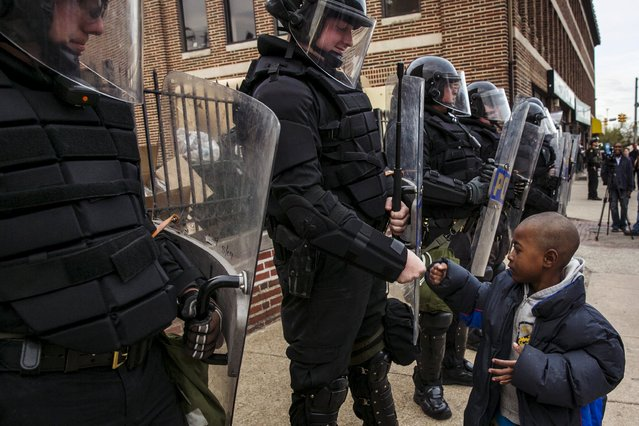 A young boy greets police officers in riot gear during a march in Baltimore, Maryland May 1, 2015 following the decision to charge six Baltimore police officers – including one with murder – in the death of Freddie Gray, a black man who was arrested and suffered a fatal neck injury while riding in a moving police van, the city's chief prosecutor said on Friday. (Photo by Lucas Jackson/Reuters)
