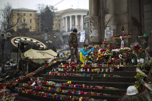 An anti-Yanukovych protester stands at a memorial for the people killed in clashes with the police at Kiev's Independence Square, the epicenter of the country's current unrest, Saturday, March 1, 2014. The pro-Russian prime minister of Ukraine's restive Crimea is claiming control of all military forces, police and other security services in the region. In a statement reported by local and Russian news agencies on Saturday, Sergei Aksenov declares that the armed forces, the police, the national security service and border guards will answer only to his orders. (Photo by Emilio Morenatti/AP Photo)
