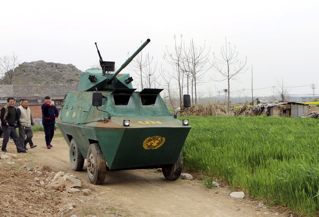Villagers look on as a homemade armored vehicle, built by local 35-year-old farmer Liu Shijie (in the vehicle), drives on a dirt road at a village in Huaibei, Anhui province, China April 7, 2015. (Photo by Reuters/Stringer)