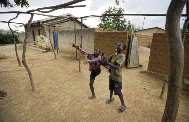 Children play with a ball made from plastic bags in the street outside their houses in the village of Mbyo, near Nyamata, in Rwanda Thursday, April 4, 2019. Rwanda will commemorate on Sunday, April 7, 2019 the 25th anniversary of when the country descended into an orgy of violence in which some 800,000 Tutsis and moderate Hutus were massacred by the majority Hutu population over a 100-day period in what was the worst genocide in recent history. (Photo by Ben Curtis/AP Photo)