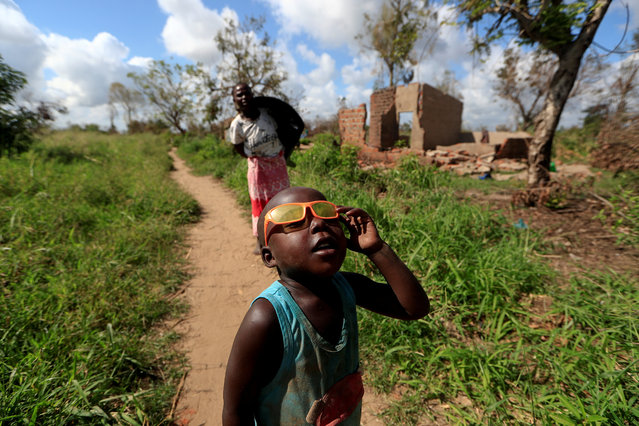 """Ester Thoma walks past her damaged house as a boy plays with his glasses in the aftermath of Cyclone Idai, in the village of Cheia, which means """"Flood"""" in Portuguese, near Beira, Mozambique April 1, 2019. (Photo by Zohra Bensemra/Reuters)"""
