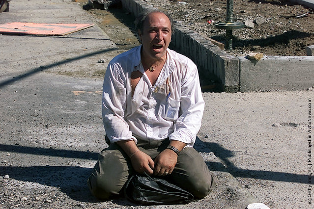 A survivor sits outside the World Trade Center after two planes hit the building September 11, 2001 in New York City