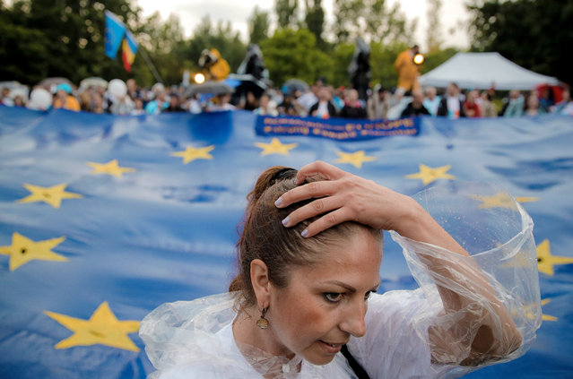 A woman runs her hand through her hair, backdropped by a European Union flag, during a 2020 USR PLUS alliance European Parliament elections rally, in Bucharest, Romania, Friday, May 24, 2019. Romanians will vote on Sunday, May 26, in the European Parliament elections. (Photo by Vadim Ghirda/AP Photo)