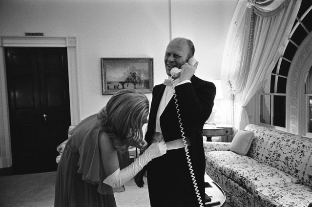 President Gerald R. Ford takes a phone call while his daughter Susan Ford adjusts her father's cummerbund before a white tie diplomatic reception on October 5, 1974, in Washington, D.C. (Photo by David Hume Kennerly/ Getty Images)