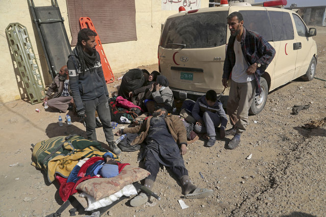 Displaced civilians, who were injured by mortars fired by Islamic State militants as they fled their homes, wait to be taken to a hospital after receiving first aid in a field clinic, in western Mosul, Iraq, Sunday, February 26. 2017. Iraqi militarized police captured a neighborhood on the western side of Mosul on Sunday amid fierce clashes with Islamic State militants, as thousands of people continued to flee the battle to government-controlled areas, security officials said. (Photo by Khalid Mohammed/AP Photo)
