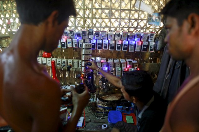 Rohingya Muslims charge their phone batteries in a shop at a refugee camp outside Sittwe, Myanmar May 21, 2015. Picture taken May 21, 2015. (Photo by Soe Zeya Tun/Reuters)