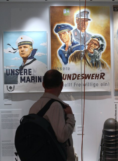 A visitor looks at post-World War II German military recruitment posters