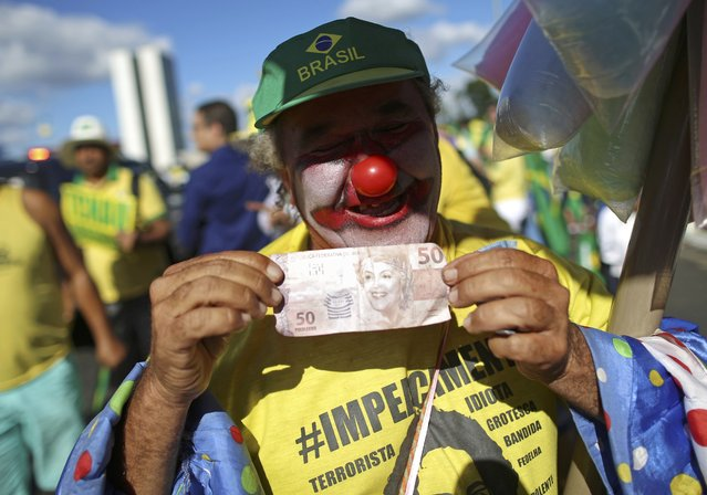 A demonstrator for the impeachment of President Dilma Rousseff holds up a mock 50 real bill with Rousseff's face on it, as the Lower House of Congress voted in Brasilia, Brazil April 17, 2016. (Photo by Adriano Machado/Reuters)