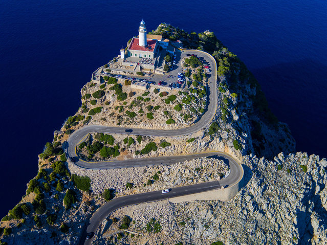 Crowning a Mediterranean cliff, the Formentor Lighthouse stands atop a serpentine ribbon of Mallorcan asphalt. (Photo by Chase Guttman/Caters News)