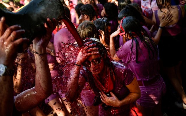 A reveler is covered in wine as people take part in a wine battle, in the small village of Haro, northern Spain, Saturday, June 29, 2019. Hundreds of revelers participate in this famous summer battle throwing thousands of liters of red wine over each other. (AP Photo/Alvaro Barrientos)