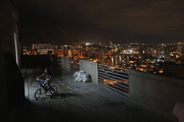 """A girl rides a bicycle on a balcony in the """"Tower of David"""" skyscraper in Caracas. (Photo by Jorge Silva/Reuters)"""