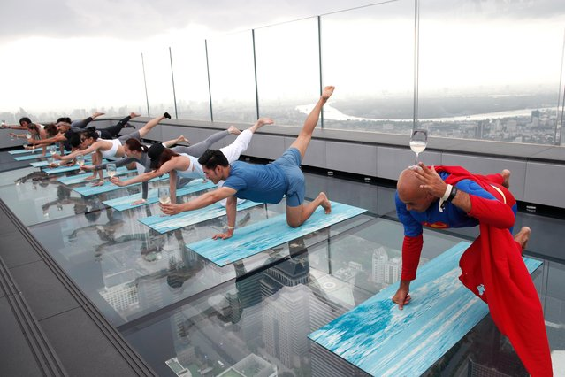 Yoga enthusiasts perform during a Wine Yoga class at the King Power Mahanakhon skyscraper in Bangkok, Thailand, 07 July 2019. The wine yoga combines the joy of drinking wine with traditional yoga poses with participants balancing a glass of wine on their bodies as well as sipping and toasting the alcoholic beverage. (Photo by Rungroj Yongrit/EPA/EFE)