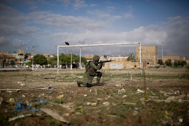 A navy soldier patrols on a soccer field during an operation to occupy the Mare slum complex in Rio de Janeiro, Brazil, April 5, 2014. More than 2,000 Brazilian Army soldiers moved into the Mare slum complex April 5, 2014 in a bid to improve security and drive out the heavily armed drug gangs that have ruled the sprawling slum for decades. (Photo by Felipe Dana/AP Photo)