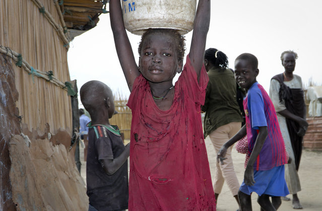 In this photo taken Sunday, December 9, 2018, a young girl carries water on her head in Koythiey displaced person's camp on the outskirts of Bentiu town in South Sudan. Six months ago planning ahead in civil war-torn South Sudan seemed impossible but now, after warring sides signed a new peace deal in September that the government vows will hold, some are starting to rebuild their lives. (Photo by Sam Mednick/AP Photo)