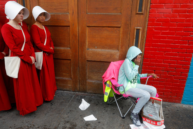 "Women dressed as handmaids, promoting the Hulu original series ""The Handmaid's Tale"", stand along a public street during the South by Southwest (SXSW) Music Film Interactive Festival 2017 in Austin, Texas, U.S., March 11, 2017. (Photo by Brian Snyder/Reuters)"