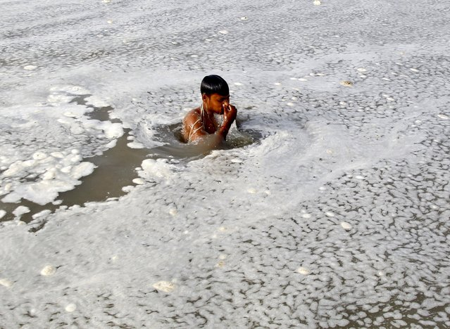 A Hindu devotee takes a dip in the polluted water of the Ganges river in Allahabad, India, July 5, 2015. (Photo by Jitendra Prakash/Reuters)