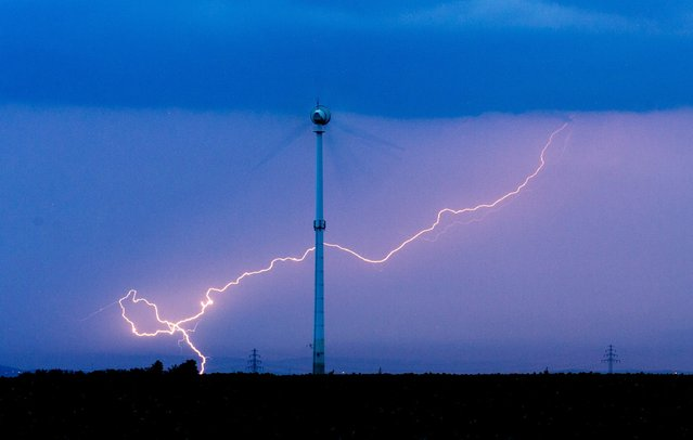 A lightning is seen striking behind a wind turbine in Sehnde, Germany, 05 July 2015. (Photo by Julian Stratenschulte/EPA)