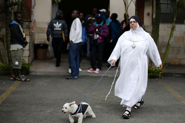 A nun walks her dog past Haitian immigrants at the Nossa Senhora da Paz Catholic church, where the immigrants are staying in a shelter, in the Glicerio neighborhood of Sao Paulo. (Photo by Nacho Doce/Reuters)