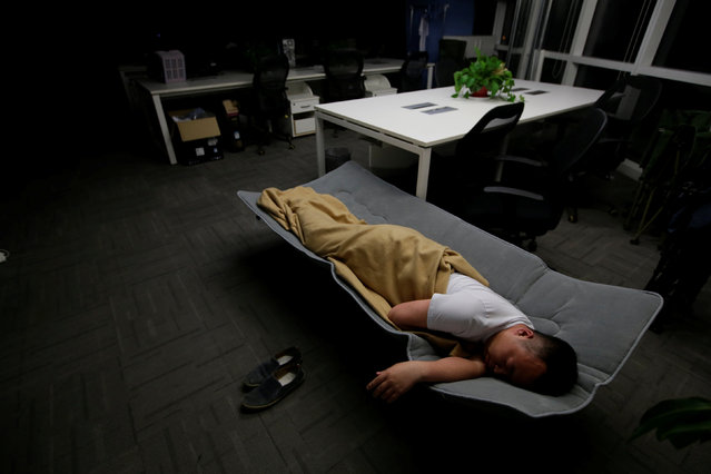 Ma Zhenguo, a system engineer at RenRen Credit Management Co., sleeps on a camp bed at the office after finishing work early morning, in Beijing, China, April 27, 2016. (Photo by Jason Lee/Reuters)