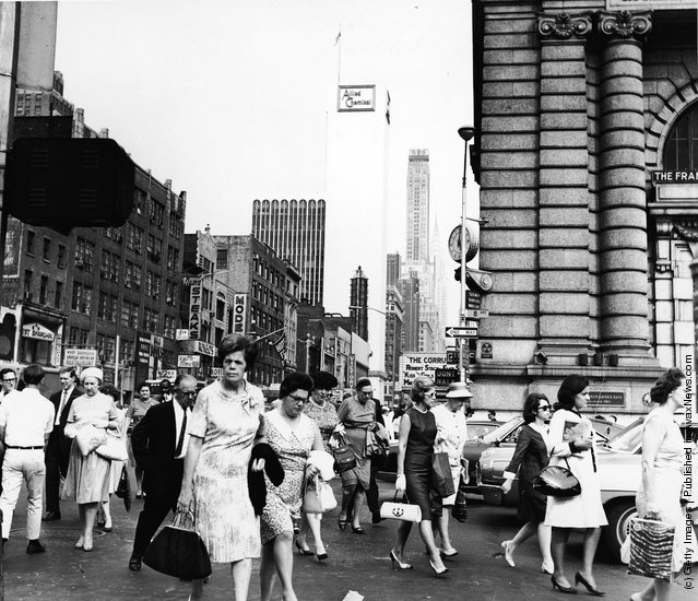 Crowds of pedestrians walk at the intersection of Eighth Avenue and 42nd Street, with the Allied Chemical building visible in the background, New York City, circa 1962