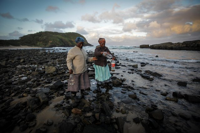 Women collect sea water near Coffee Bay, in South Africa's Eastern Cape, 06 May 2014, which is also one of the poorest and most crime affected areas in the country. On 07 May 2014, South Africans will take to the polls for the Country's second decade of democratic elections. (Photo by Kevin Sutherland/EPA)